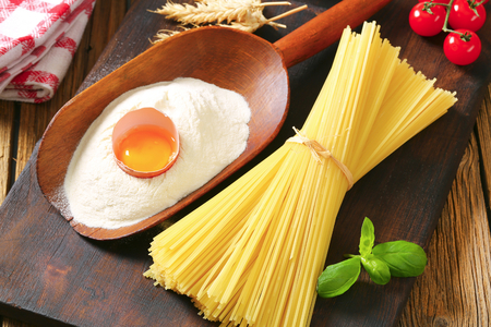 thin shell: Bundle of dried spaghetti, scoop of flour and fresh egg Stock Photo