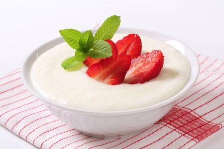 Bowl of semolina pudding with fresh strawberries