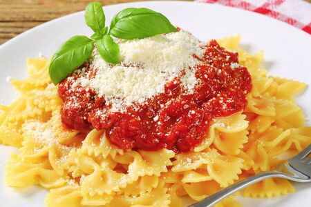 thick: Bow-tie pasta with thick tomato sauce and parmesan Stock Photo