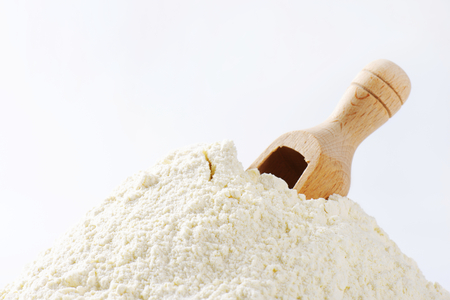 wooden scoop: Pile of finely ground flour and wooden scoop Stock Photo