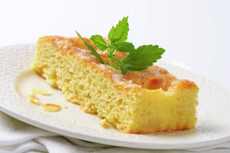 sponge cake: Slice of sponge cake topped with almond flakes Stock Photo