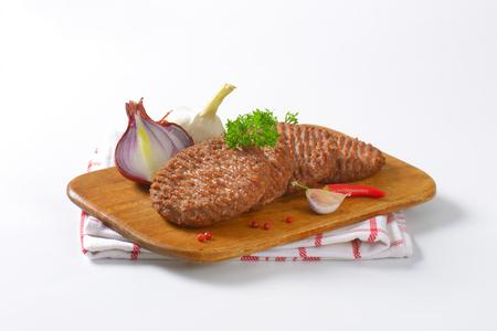 carne asada: La parrilla empanadas hamburguesa de carne en la tabla de cortar Foto de archivo