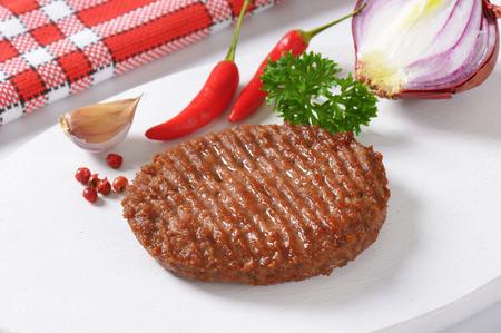carne asada: Carne a la parrilla de Burger Patty en tabla para cortar Foto de archivo