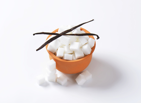 sugar cubes: White sugar cubes in terracotta dish and two dried vanilla beans