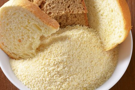breadcrumbs: Pieces of stale bread and pile of finely ground bread crumbs