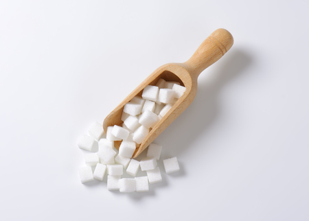 sucrose: White sugar cubes in wooden scoop Stock Photo