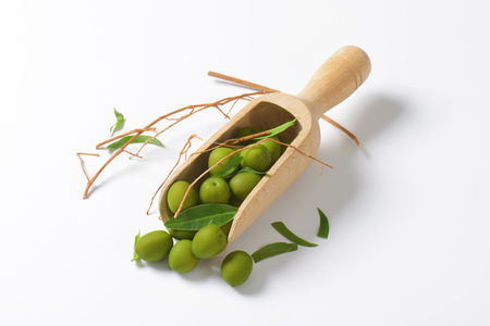 wooden scoop: Raw green olives on wooden scoop Stock Photo