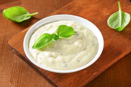 Krémová zálivka z majonézy, podmáslí, česnek, bylinky, koření a strouhaným sýrem Reklamní fotografie - 43312956