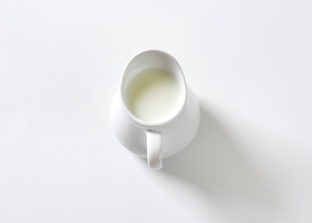Fresh milk in white pitcher Imagens