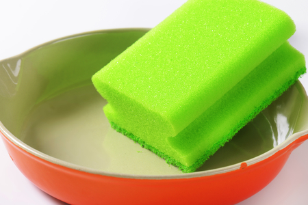green kitchen sponge on ceramic baking dish