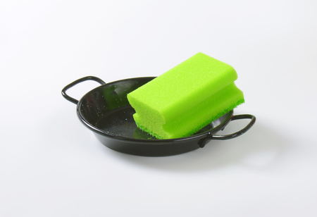 green kitchen sponge on black skillet
