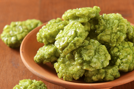 nibbles: detail of wasabi crackers in ceramic bowl Stock Photo