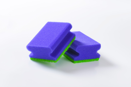 two blue kitchen sponges on white background