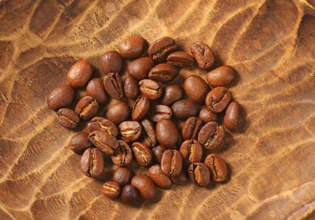 fairtrade: handful of coffee beans in wooden bowl