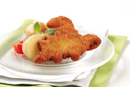 crumbing: Fried breaded fish and potatoes - closeup