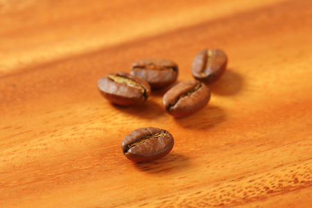 fairtrade: Five roasted coffee beans on wooden table Stock Photo