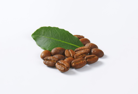 handful: Handful of roasted coffee beans on white background Stock Photo