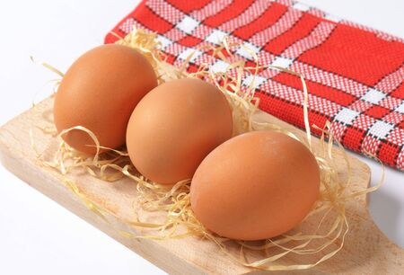 cutting: fresh eggs on wooden cutting board Stock Photo