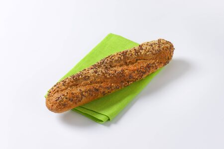 place mat: fresh baguette bread with seeds on green place mat