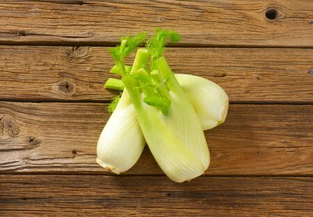 bulb and stem vegetables: bulbs of fresh fennel on wooden table