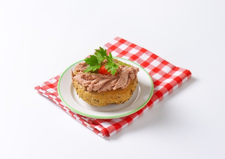 dishtowel: fresh bun with pate, cherry tomato and parsley on white plate and checkered dishtowel