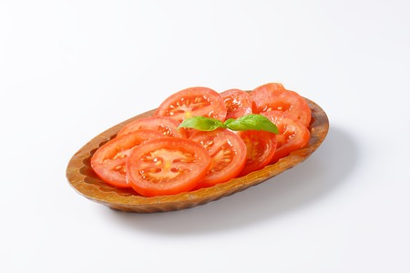 tomato slices: bowl of tomato slices on white background