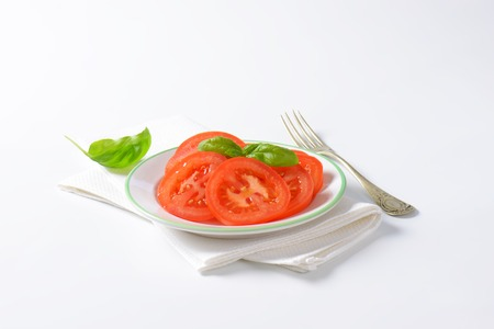 placemat: tomato salad with basil on white plate and placemat