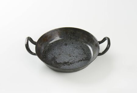 skillet: empty black skillet with handles on white background Stock Photo