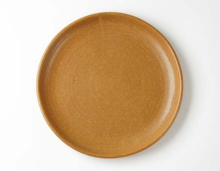 overhead: empty brown plate on white background
