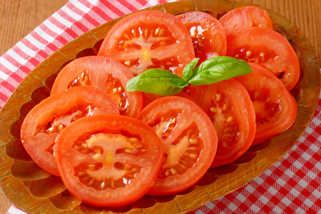 tomato slices: detail of tomato slices and fresh basil on oval wooden plate and checkered dishtowel Stock Photo