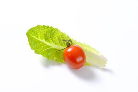 romaine lettuce: leaf of romaine lettuce and cherry tomato on white background Stock Photo
