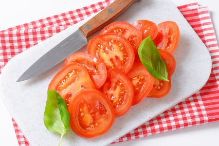 dishtowel: tomato slices and kitchen knife on white cutting board and checkered dishtowel Stock Photo