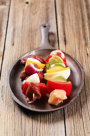 cast iron red: Raw Shish kebabs on a cast iron skillet