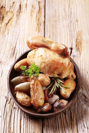 baked chicken: Cooked chicken served with baked potatoes and vegetables