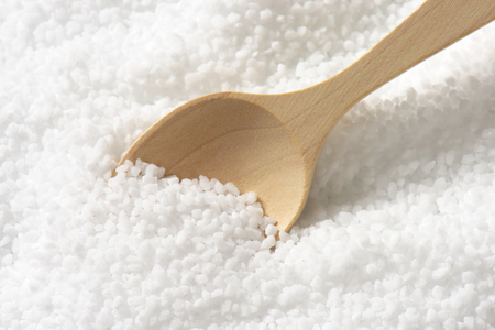 mineral salt: Detail of coarse grained salt and wooden spoon Stock Photo