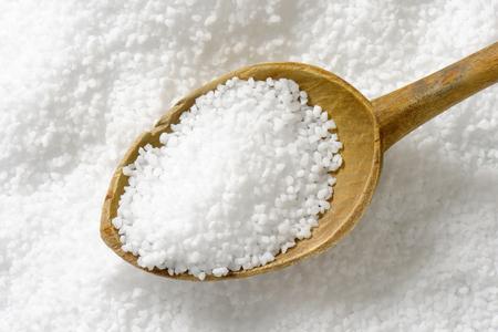 Detail of coarse grained salt and wooden spoon Foto de archivo