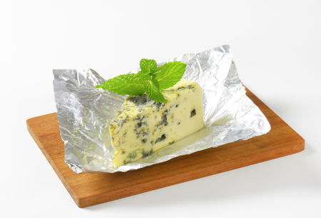 Wedge of French blue cheese on foil 写真素材