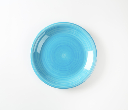 Coup shaped ceramic plate with a blue color glaze