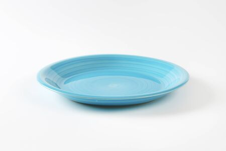 rimless: Coup shaped ceramic plate with a blue color glaze