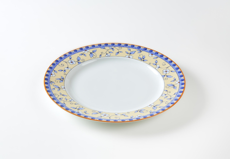 country style: Country style dinner plate with floral design border and brown trim Stock Photo