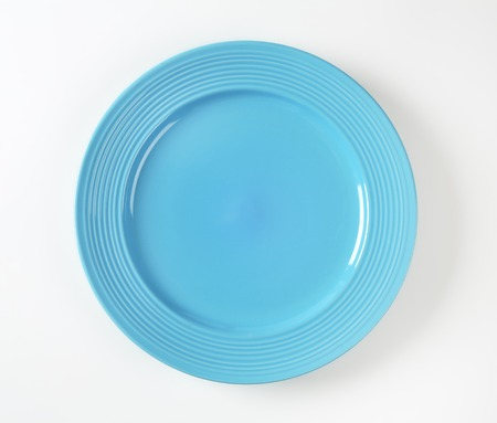 on a white background: Blue glazed dinner plate with embossed concentric rings on the edge
