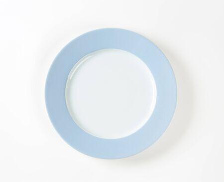 plato de comida: plato blanco con borde azul sobre fondo blanco