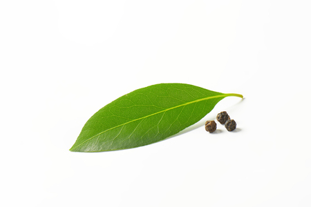 Fresh bay leaf and black peppercorns on white background