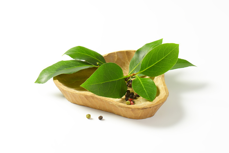 sprig: Sprig of bay leaves and peppercorns in triangle wooden bowl