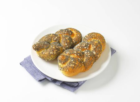 braided: Braided bread rolls topped with poppy seeds and salt