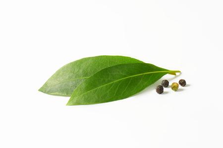 Verse laurierbladeren en zwarte peperbollen op witte achtergrond