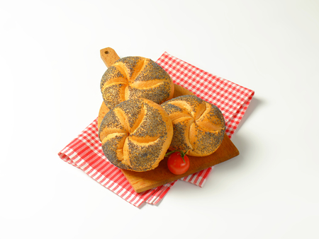 dishtowel: fresh poppy seed buns on wooden cutting board and checkered dishtowel