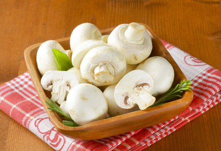 halved  half: Fresh button mushrooms in square wooden bowl Stock Photo