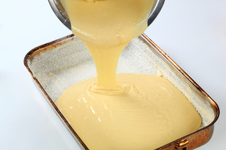 greased: pouring batter into baking pan greased with butter and covered with coconut