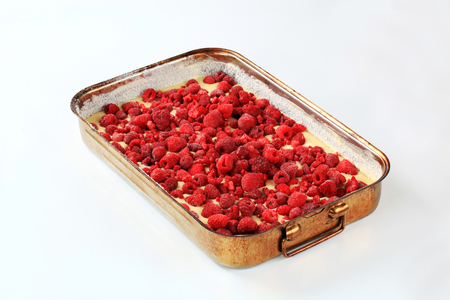 baking tray: raw cake batter with frozen raspberries in baking tray ready to be baked
